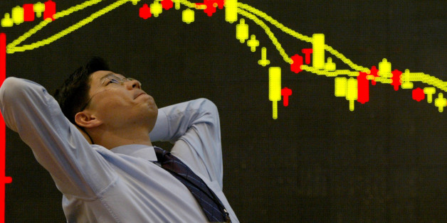 FILE PHOTO: A South Korean employee of a securities firm reacts in front of a graph showing stock price in Seoul March 11, 2003.  REUTERS/Kim Kyung-Hoon/File photo