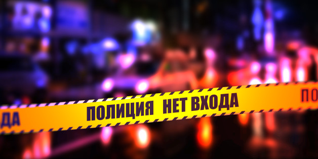 A night time street scene with focus on safety Police tape in Russian 'Police No Entry'.