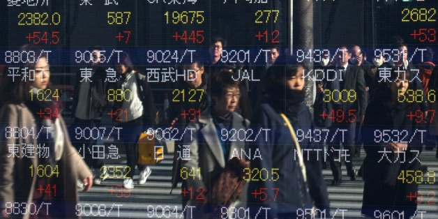 Pedestrians are reflected in an electric quotation board flashing stock prices on the Tokyo Stock Exchange in Tokyo on January 4, 2017.Tokyo shares surged in the morning on January 4 on the first trading day of 2017, following gains on Wall Street driven by optimism over the US economy. / AFP / KAZUHIRO NOGI        (Photo credit should read KAZUHIRO NOGI/AFP/Getty Images)