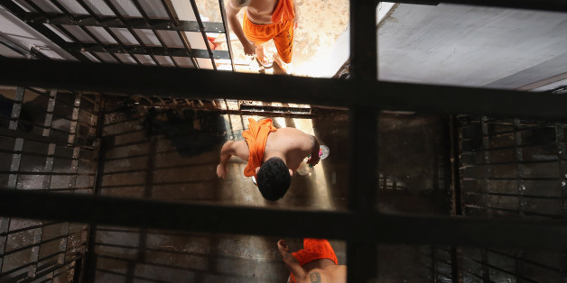 SAO LUIS, BRAZIL - JANUARY 27:  Inmates walk from their cells towards a recreation area in the Pedrinhas Prison Complex, the largest penitentiary in Maranhao state, on January 27, 2015 in Sao Luis, Brazil. Previously one of the most violent prisons in Brazil, Pedrinhas has seen efforts from a new state administration, new prison officials and judiciary leaders from Maranhao which appear to have quelled some of the unrest within the complex. In 2013, nearly 60 inmates were killed within the complex, including three who were beheaded during rioting. Much of the violence stemmed from broken cells allowing inmates and gang rivals to mix in the patios and open spaces of the complex. Officials recently repaired and repopulated the cells allowing law enforcement access and decreasing violence among prisoners, according to officials. Other reforms include a policy of custody hearings and real-time camera feeds. According to officials there have been no prisoner on prisoner killings inside the complex in nearly four months. Critics believe overcrowding is one of the primary causes of rioting and violence in Brazil's prisons. Additionally, overcrowding has strengthened prison gangs which now span the country and contol certain peripheries of cities including Rio de Janeiro, Sao Paulo and Sao Luis. Brazil now has the fourth-largest prison population in the world behind the U.S., Russia and China. The population of those imprisoned had quadrupled in the past twenty years to around 550,000 and the country needs at least 200,000 new incarceration spaces to eliminate overcrowding. A vast increase in minor drug arrests, a dearth of legal advice for prisoners and a lack of political will for new prisons have contributed to the increases.  (Photo by Mario Tama/Getty Images)