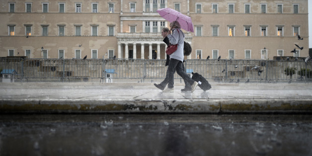 Tourists walk under the rain in front of the Greek Parliament in Athens on November 6, 2013. AFP PHOTO / ARIS MESSINIS        (Photo credit should read ARIS MESSINIS/AFP/Getty Images)