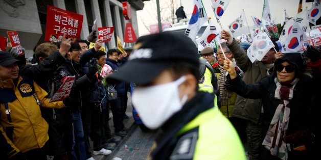 Supporters (R) of South Korean President Park Geun-hye march past a group of people (L) demanding President Park Geun-hye's resignation, during a protest opposing her impeachment in Seoul, South Korea December 17, 2016.  REUTERS/Kim Hong-Ji