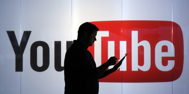 A man is seen as a silhouette as he checks a mobile device whilst standing against an illuminated wall bearing YouTube Inc.'s logo in this arranged photograph in London, U.K., on Tuesday, Jan. 5, 2016. YouTube Inc. provides consumer media and entertainment through its website. Photographer: Chris Ratcliffe/Bloomberg via Getty Images
