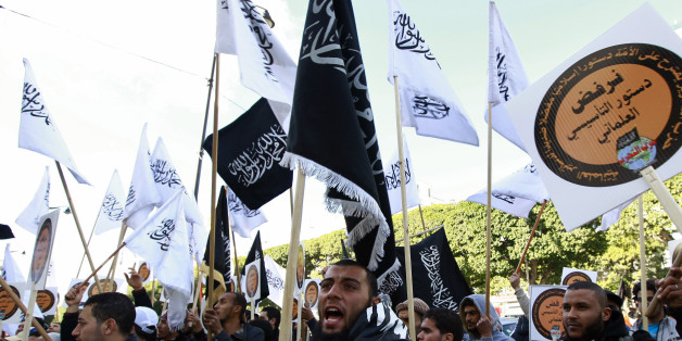 "Supporters of the Islamist party ""Hizb Ut-Tahrir"" movement wave flags during a rally at central Habib Bourguiba Avenue, as they protest against the new Constitution, in Tunis January 24, 2014. REUTERS/Anis Mili (TUNISIA - Tags: CIVIL UNREST POLITICS)"
