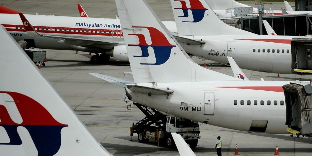 Malaysia Airlines ground staff walk past Malaysia Airlines aircraft parked on the tarmac at the Kuala Lumpur International Airport in Sepang on June 20, 2016. Malaysia is hosting a two-day meeting with Australia and China to discuss next steps in the fruitless search for missing Malaysia Airlines flight MH370. / AFP / MANAN VATSYAYANA        (Photo credit should read MANAN VATSYAYANA/AFP/Getty Images)