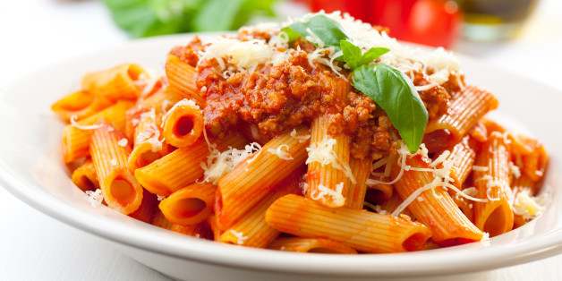 Plate of penne bolognese with ingredients in the background.