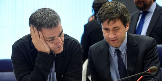 Greek Finance Minister Euclid Tsakalotos (L) listens to a Greek advisor during an Eurogroup meeting in Luxembourg on October 10, 2016.