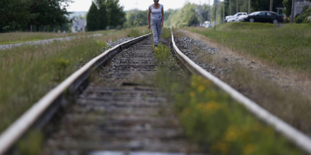 A woman walks on the railway close to the train wreck in Lac-Megantic July 13, 2013. The crude oil freight train that derailed and blew up in the small town of Lac-Megantic early on Saturday morning was traveling far too fast when it went off the rails, investigators told reporters on Tuesday.  REUTERS/Mathieu Belanger (CANADA - Tags: DISASTER TRANSPORT)