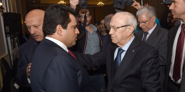 Tunisian newly-elected President Beji Caid Essebsi (C) greets the leader of the Free Patriotic Union (UPL) and former presidential candidate Slim Riahi (L) as part of a meeting with political parties who supported him on December 24, 2014 in Tunis. Essebsi said the day before that the country has turned the page on dictatorship after a presidential vote that European observers hailed as 'credible and transparent'. AFP PHOTO / FETHI BELAID        (Photo credit should read FETHI BELAID/AFP/Getty Images)
