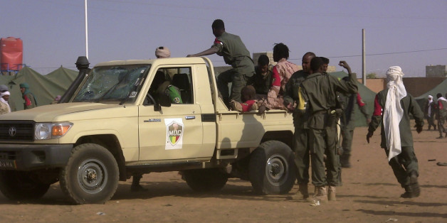 EDITORS NOTE: Graphic content / Soldiers gather at a pickup truck following a suicide bomb attack that ripped through a camp grouping former rebels and pro-government militia in Gao, in the troubled northern Mali left 50 people dead on January 18, 2017 in Gao.