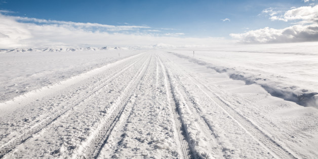 A snow covered road leads through an empty winter landscape under clear sky. Near Garrison, Utah.