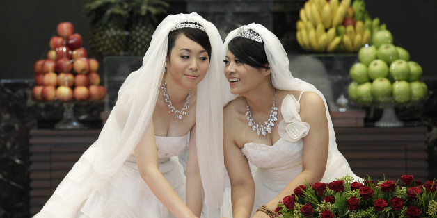 You Ya-ting (L) and Huang Mei-yu cast their stamps during their symbolic same-sex Buddhist wedding ceremony at a temple in Taoyuan county, northern Taiwan, August 11, 2012. The 30-year-old lesbian couple tied the knot after dating for seven years on Saturday in Taiwan's first same-sex Buddhist wedding. They hope this wedding will help make Taiwan the first place in Asia to legalise same-sex marriage. REUTERS/Pichi Chuang (TAIWAN - Tags: SOCIETY TPX IMAGES OF THE DAY)