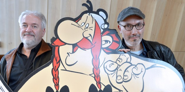 French cartoonist Didier Conrad (L), and the coauthor of the popular comic book Asterix with French cartoonist and author Albert Uderzo (unseen) writer and designer Jean-Yves Ferri pose beside a cardboard cut-out of Asterix and Obelix characters during a press conference in Paris on October 12, 2015 for the release of the new Asterix album 'Le Papyrus de Cesar' (Caesar's Papyrus). The 36th book in the Asterix series 'Le Papyrus de Cesar' (entitled in English : Asterix and the Missing Scroll), wi