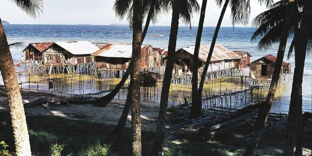 PAPUA NEW GUINEA - FEBRUARY 9: Palm trees and pile dwellings, Biak island, Papua New Guinea. (Photo by DeAgostini/Getty Images)