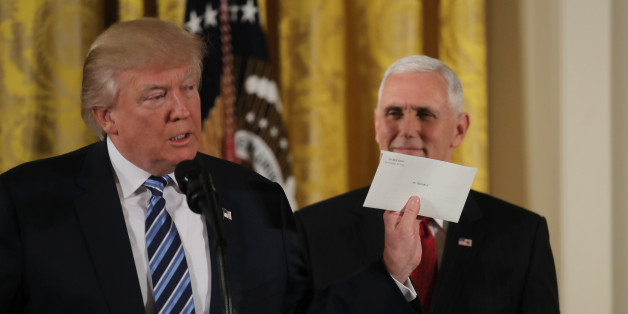 U.S. President Donald Trump shows a letter from former President Barack Obama at a swearing-in ceremony for senior staff at the White House in Washington, DC January 22, 2017. REUTERS/Carlos Barria