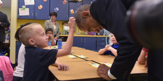 US President Barack Obama offers leans over for a boy to feel his hair during a visit to an elementary school at MacDill Air Force Base in Tampa, Florida on September 17, 2014. AFP PHOTO/Mandel NGAN        (Photo credit should read MANDEL NGAN/AFP/Getty Images)