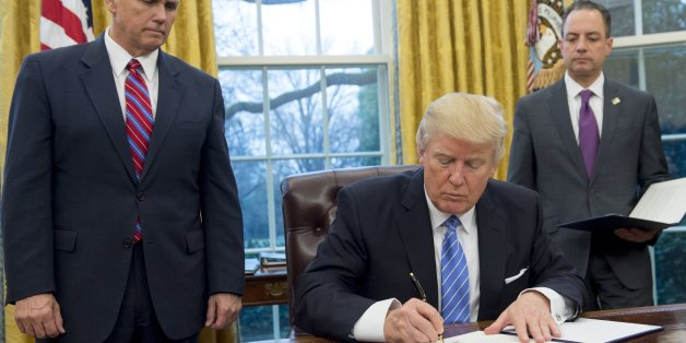 US President Donald Trump signs an executive order withdrawing the US from the Trans-Pacific Partnership alongside US Vice President Mike Pence (L) and White House Chief of Staff Reince Priebus (R) in the Oval Office of the White House in Washington, DC, January 23, 2017.Trump the decree Monday that effectively ends US participation in a sweeping trans-Pacific free trade agreement negotiated under former president Barack Obama. / AFP / SAUL LOEB        (Photo credit should read SAUL LOEB/AFP/Get