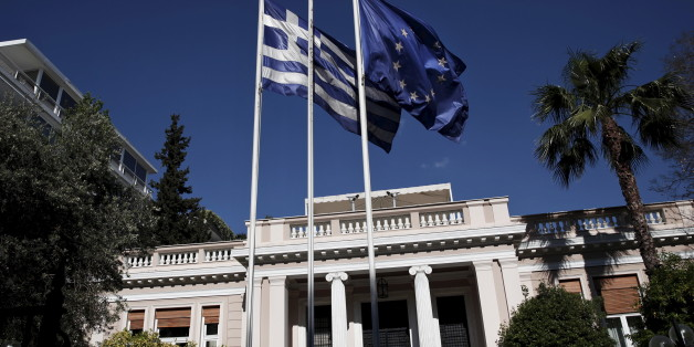 A Greek national flag and a European Union flag flutter outside the Maximos mansion as a government council at the Prime Minister's office takes place, in Athens May 13, 2015. Greece's government on Wednesday ruled out rushing to a referendum to secure public support for unpopular reforms, opting instead to make a final push for a compromise with lenders by the end of the month. REUTERS/Alkis Konstantinidis