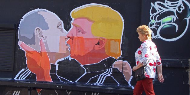 A woman walks past a mural on a restaurant wall depicting US  Presidential hopeful Donald Trump and Russian President Vladimir Putin greeting each other with a kiss in the Lithuanian capital Vilnius on May 13, 2016. Kestutis Girnius, associate professor of the Institute of International Relations and Political Science in Vilnius university, told AFP -This graffiti expresses the fear of some Lithuanians that Donald Trump is likely to kowtow to Vladimir Putin and be indifferent to Lithuanias security concerns. Trump has notoriously stated that Putin is a strong leader, and that NATO is obsolete and expensive.   / AFP / Petras Malukas        (Photo credit should read PETRAS MALUKAS/AFP/Getty Images)
