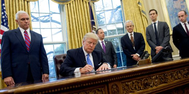 US President Donald Trump signs an executive order in the Oval Office of the White House in Washington, DC, January 23, 2017.Trump on Monday signed three orders on withdrawing the US from the Trans-Pacific Partnership trade deal, freezing the hiring of federal workers and hitting foreign NGOs that help with abortion. / AFP / SAUL LOEB        (Photo credit should read SAUL LOEB/AFP/Getty Images)