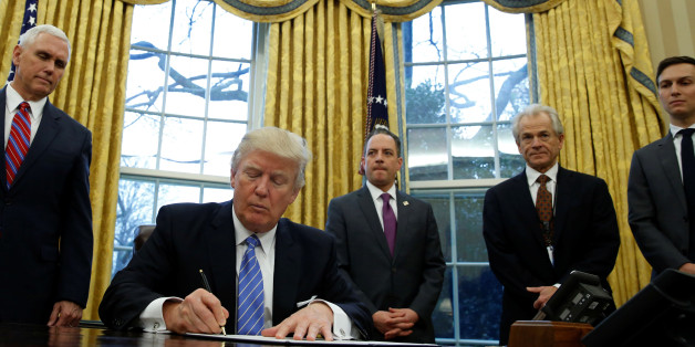 U.S. President Donald Trump, watched by (L-R) Vice President Mike Pence, White House Chief of Staff Reince Priebus, head of the White House Trade Council Peter Navarro and senior advisor Jared Kushner, signs an executive order that places a hiring freeze on non-military federal workers in the Oval Office of the White House in Washington January 23, 2017.   REUTERS/Kevin Lamarque