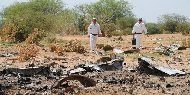 Forensics gather evidence at the crash site of the Air Algerie AH5017 in Mali's Gossi region, on July 29, 2014. France said on July 28 the pilots of the Air Algerie passenger plane that crashed in Mali, killing all 118 people on board, had asked to turn back in a new development to a complex probe into the tragedy. Reports that the crew asked to amend their route because of bad weather conditions emerged almost as soon as the tragedy came to light on July 24, but the revelation that they subsequ