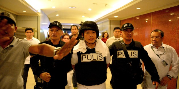 Police officer Ricky Sta. Isabel (C), one of the suspects in the kidnapping and murder of South Korean businessman Jee Ick Joo, is escorted by fellow policemen as they leave the National Bureau of Investigation (NBI) building in Manila on January 20, 2017. A South Korean businessman kidnapped by Philippine policemen under the guise of a raid on illegal drugs was murdered at the national police headquarters in Manila, authorities said Thursday. / AFP / NOEL CELIS        (Photo credit should read