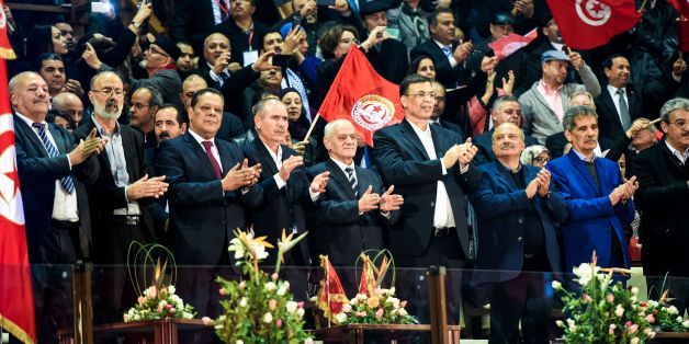 Secretary general of the General Union of Tunisian Workers (UGTT), Houcine Abbassi (5th from L), and his cabinet wave to crowds during the opening of the union's 23rd congress in the capital Tunis on January 22, 2017. / AFP / FETHI BELAID        (Photo credit should read FETHI BELAID/AFP/Getty Images)