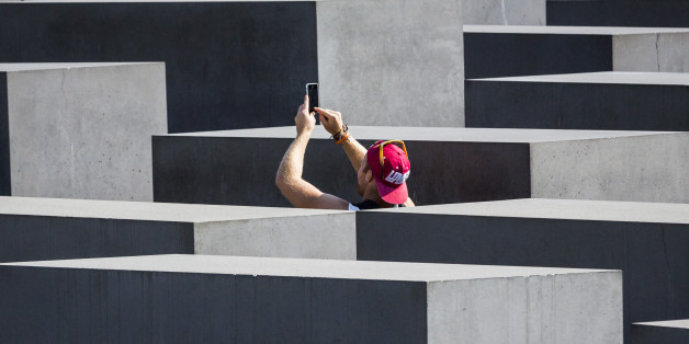 BERLIN, GERMANY - SEPTEMBER 04: Tourists taking a photo of the concrete slabs, stelae of the Memorial to the Murdered Jews of Europe on September 04, 2014, in Berlin, Germany. The monument is designed by architect Peter Eisenman and engineer Buro Happold. Photo by Thomas Trutschel/Photothek via Getty Images)***Local Caption***