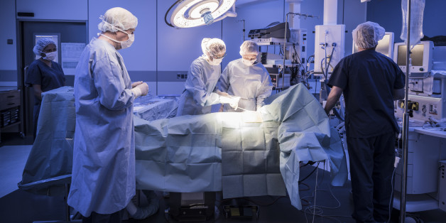 Four doctors in hospital operating room with patient lying on operating table. Surgical lights shining on medical team performing operation on patient