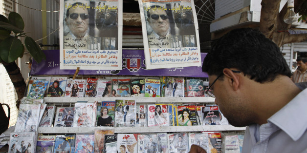 A man reads the headlines of local newspapers in Cairo June 3, 2012, a day after former leader Hosni Mubarak was handed a life prison sentence. Egyptian pro-democracy campaigners called for a new uprising on Sunday, enraged that a court had spared Mubarak his life over the killing of protesters during the street revolt that ended his three-decade rule. REUTERS/Ammar Awad (EGYPT - Tags: POLITICS CIVIL UNREST)