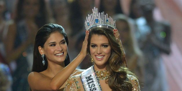 Miss Universe contestant Iris Mittenaere (R) of France is crowned the new 2017 winner by former Miss Universe Pia Wurtzbach of the Philippines (L) during the Miss Universe pageant at the Mall of Asia Arena in Manila on January 30, 2017.France was crowed Miss Universe on January 30 in a glitzy spectacle free of last year's dramatic mix-up but with a dash of political controversy as finalists touched on migration and other hot-button global issues. / AFP / TED ALJIBE        (Photo credit should re