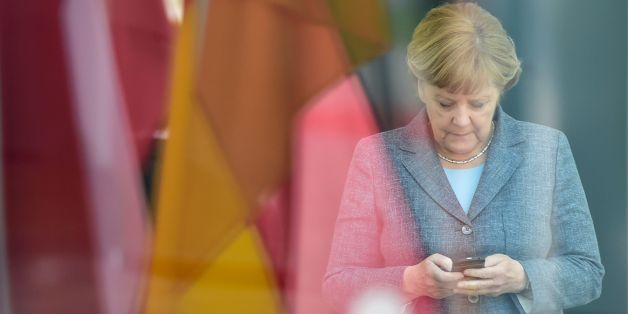 German chancellor Angela Merkel looks at her smartphone while waiting at the chancellery for the arrival of the Latvian Prime Minister in Berlin, on April 29, 2016. / AFP / John MACDOUGALL        (Photo credit should read JOHN MACDOUGALL/AFP/Getty Images)