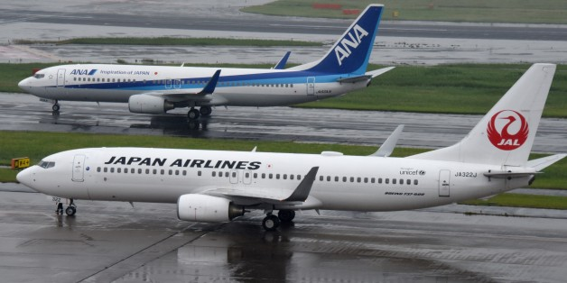 All Nippon Airways (ANA/top) and Japan Airlines (JAL/bottom) aircraft are seen at Haneda Airport in Tokyo on April 28, 2016. The Japanese airline will announce its financial results for fiscal year 2015 ended March 2016. / AFP / TORU YAMANAKA        (Photo credit should read TORU YAMANAKA/AFP/Getty Images)