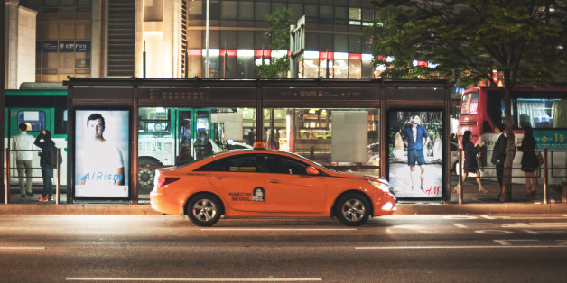 Seoul, Republic of Korea - May 12, 2014: Orange taxis cruising the streets at night Jamsil range