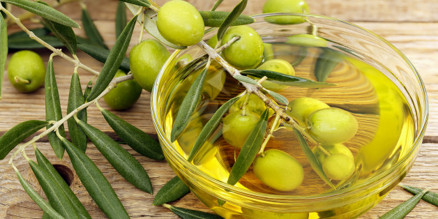 olive tree branch dipped in bowl of olive oil