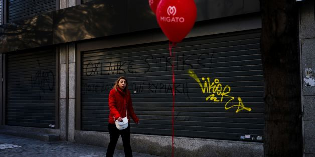 A woman walks in front of a closed shop with a graffiti tag reading 'strike' in the center of Athens in January 8, 2017. / AFP / Angelos Tzortzinis        (Photo credit should read ANGELOS TZORTZINIS/AFP/Getty Images)