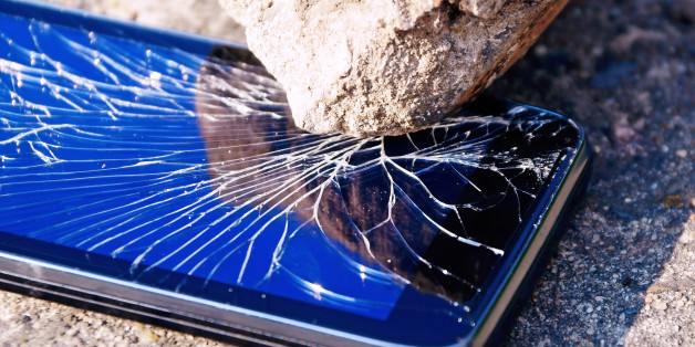 Cracked mobile smartphone savagely smashed by a stone.