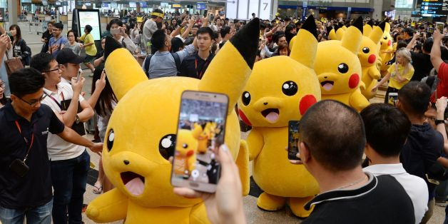 Fans gather to watch the Pokemon Go virtual reality game mascot Pikachu parade during a promotional event at the Changi International airport terminal in Singapore on November 18, 2016. Hundreds of Pokemon fans gathered at Changi Airport's Terminal 3 on November 18 to watch the Pikachu parade and Gingerbread House display which are part of the airport's year-end events. / AFP / Roslan RAHMAN        (Photo credit should read ROSLAN RAHMAN/AFP/Getty Images)