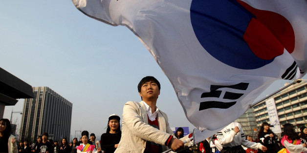 SEOUL, SOUTH KOREA - FEBRUARY 22:  A South Korean student waves national flags during an anti-Japan rally on February 22, 2014 in Seoul, South Korea. South Korea and Japan are making claim to a set of islands controlled by South Korea, Dokdo or Takeshima, located in the East Sea. The rally was taking place after the Japanese government declared today to be Takeshima Day, further fueling a long-standing territorial row between the two countries.  (Photo by Chung Sung-Jun/Getty Images)