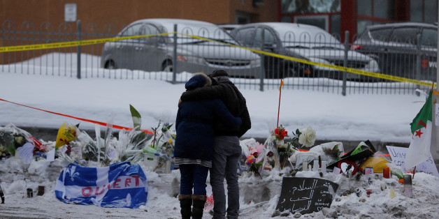 Azzedine Najd (R) and his wife Fadwa Achmaoui look at the memorial near the site of a fatal shooting at the Quebec Islamic Cultural Centre in Quebec City, Canada January 31, 2017. REUTERS/Mathieu Belanger