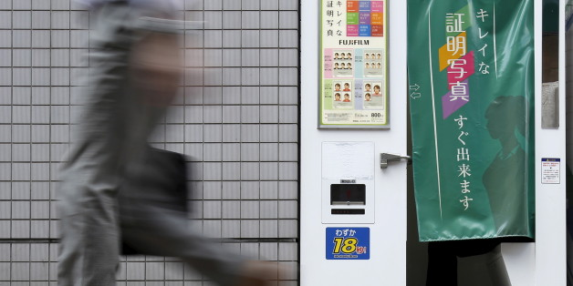 A pedestrian walks past an ID photo machine box as a man sits inside at a business district in Tokyo, September 15, 2015. The Bank of Japan said on Tuesday that slowing emerging market demand was putting further strains on the economy but held off on expanding stimulus, preserving its limited policy options in case an expected U.S. rate hike sparks more global volatility. REUTERS/Yuya Shino
