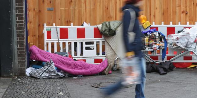 Mann geht an einem Obdachlosen in Berlin vorbei