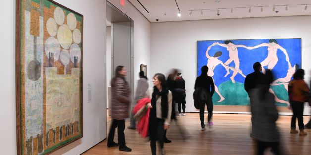 Visitors look at artwork by Iranian painter and sculptor Charles Hossein Zenderoudi -- K+L+32+H+4 Mon pere et moi, 1962' (L)--  at The Museum of Modern Art on February 3, 2017 in New York City.The famed New York art museum has joined the throng of protests against US President Donald Trump's travel ban by replacing Western art with pieces by Iranian, Iraqi and Sudanese-born artists. The Museum of Modern Art said the seven works by Sudanese painter Ibrahim el-Salahi, the late Iraqi-born architect