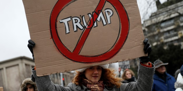 TOPSHOT - An anti-Trump protester holds a sign during a demonstration in Paris, on February 4, 2017.
