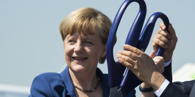 German Chancellor Angela Merkel holds scissors during the opening ceremony of the International Air Show ILA in Schoenefeld near Berlin on May 20, 2014. Turkey is partner country of this year's aerospace trade show that runs until May 25, 2014. AFP PHOTO / JOHANNES EISELE        (Photo credit should read JOHANNES EISELE/AFP/Getty Images)
