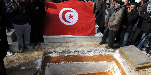 Mourners hold a Tunisian flag as they gather around the grave of assassinated opposition leader Chokri Belaid during his burial at El-Jellaz cemetery in a suburb of Tunis on February 8, 2013. Tunisian police fired tear gas and clashed with protesters as tens of thousands joined the funeral of Belaid whose murder plunged the country into new post-revolt turmoil. AFP PHOTO/FETHI BELAID        (Photo credit should read FETHI BELAID/AFP/Getty Images)