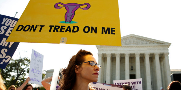 Demonstrators hold signs outside the U.S. Supreme Court as the court is due to issue its first major abortion ruling since 2007 against a backdrop of unremitting divisions among Americans on the issue and a decades-long decline in the rate at which women terminate pregnancies in Washington, U.S. June 27, 2016. REUTERS/Kevin Lamarque