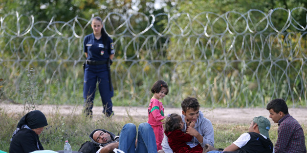 Migrants sit on the field as they were stopped by the Hungarian police after illegally crossing from Serbia to Hungary near the village of Asttohatolom, Hungary, September 16, 2015.  Hungary's right-wing government shut the main land route for migrants into the European Union on Tuesday, taking matters into its own hands to halt Europe's influx of refugees. REUTERS/Dado Ruvic