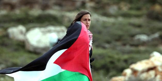 A woman holds up the Palestinian flag during clashes with Israeli soldiers close to the Jewish settlement of  Beit El, in the Israeli occupied West Bank, on March 11, 2014. The clashes broke out following the funeral of Saji Sayel Darwish who was killed the previous day by Israeli soldiers during fighting with stone throwers near the West Bank administrative centre of Ramallah. AFP PHOTO / ABBAS MOMANI        (Photo credit should read ABBAS MOMANI/AFP/Getty Images)